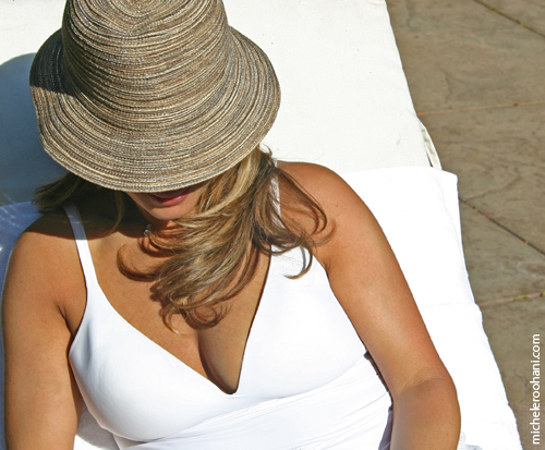 sun worshipper in white bathing suit and hat michele roohani